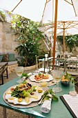 Tables laid under a parasol in a Mediterranean courtyard