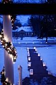 Mit Windlichttüten und beleuchteter Girlande romantisch geschmückter Vorgarten in der Abenddämmerung