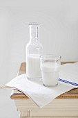 Almond milk in a glass and a bottle on a wooden table