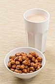 A cup of hazelnut milk and a bowl of hazelnuts