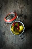 Eingelegte Gurken mit Chilis im Einmachglas auf Holztischplatte