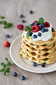 A stack of waffles with raspberries, blueberries and whipped cream