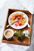 Waffles with strawberries and coffee on a breakfast tray on a bed