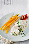 Steamed chicken breast with carrots on a creamy avocado sauce