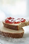 Roggenbrotscheibe mit Marmelade, angebissen