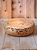 A wheel of cheese on a wooden board (Vogesen, Alsace)