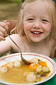 A little girl eating vegetable soup with yeast dumplings