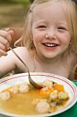 Kleines Mädchen isst Gemüsesuppe mit Hefeklösschen