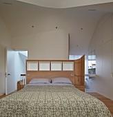 Schlafzimmer im Dachgeschoss mit weißem Einbauschrank und Bad Ensuite im Designerstil, organische Deckengestaltung und maßgeschreinerter Raumteiler als Bettkopfteil