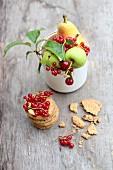 Frisches Obst im Becher und gestapelte Kekse