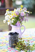 A jar of blueberries with a jug of meadow flowers on a garden table