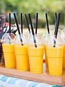 Marktstand mit frischem Mangolassi in Plastikbechern