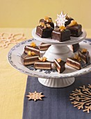 Dominosteine (chocolate covered sweets with marzipan and gingerbread) on a cake stand for Christmas