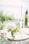 Weisses Blumensträusschen und Kerzen auf Hochzeitstafel im Freien (Ravello, Italien)