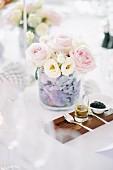 Blumensträusschen auf Hochzeitstafel im Freien