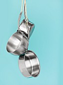 Three stainless steel pans hanging up