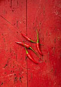 Four red Bird's Eye chillis on a red surface