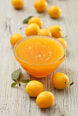 Yellow plum jam in a glass bowl