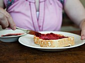 A woman spreading strawberry jam onto a slice of toast