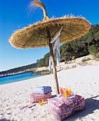 Sitzkissen & Getränke unter Strohsonnenschirm am Sandstrand