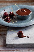 Cherries being dipped into chocolate