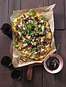 Polenta pizza with mushrooms and lamb's lettuce on baking paper