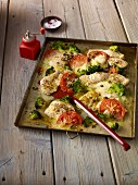 Turkey escalope on a baking tray with broccoli and tomatoes