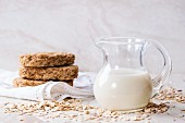 A jug of oat milk, oats and crispbread on a white marble surface