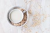 Eine Tasse Hafermilch in Schüssel mit Haferflocken auf Marmorfläche (Draufsicht)