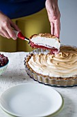 A woman slicing raspberry meringue tart