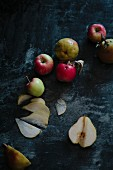 Apples and pears on a dark surface