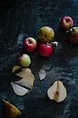 Äpfel und Birnen auf dunklem Hintergrund