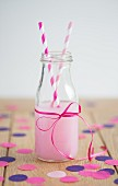 A strawberry drink in a bottle with straws