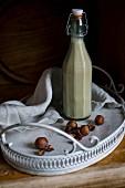 Veganer Haselnussdrink in Glasflasche auf Vintage-Tablett