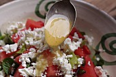 Dressing being poured onto a watermelon salad with feta cheese and mint