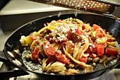 Parmesan auf Nudelgericht reiben