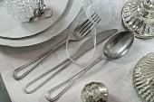 Silberbesteck mit ausgefrästen Griffen auf gedecktem Tisch