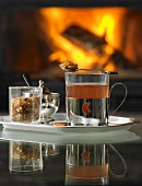Hot tea with rock sugar on a tray in front of an open fire