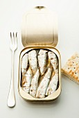 An open tin of sardines with a fork and crackers