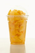 Sliced pineapple in a plastic cup