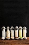 Various types of milk substitutes in bottles with their ingredients: coconut milk, soya milk, rice milk, almond milk, almond milk, Edamame milk and oat milk