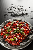 Black pizza made with peppers, tomatoes, olives, mozzarella and charcoal powder