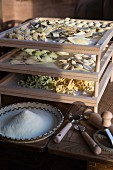 Fresh handmade pasta drying on a wooden rack with a bowl of cornmeal and pasta-making tools in the forground
