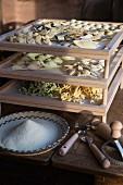 Trocknende, frische Nudeln auf einem Holzgestell, davor eine Korbschale voller Maismehl und Utensilien für die Nudelherstellung