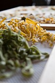 Fresh, handmade tagliatelle pasta drying on a rack
