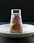 A layered salad in an upside down glass on vinaigrette