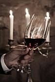 Weihnachten im Weinkeller: Hand hält Rotweinglas vor Kerzenleuchter