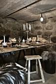 Weihnachten im Weinkeller: gedeckter rustikaler Holztisch mit Wein und Kerzen
