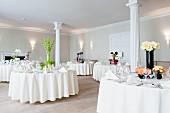 Festlich gedeckte Hochzeitstische in Raum mit weissen Säulen