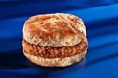 A slice of breaded sausage in an American biscuit